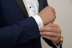 Young white Caucasian male in black tie, fixing his cuff links sign of sprezzatura and elegance stock image