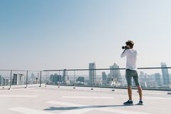 White man taking cityscape photo on building rooftop on sunny day. Photography hobby, gadget technology, leisure activity concept Stock Image