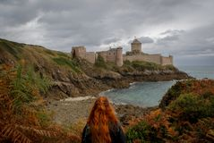 Young white Caucasian woman with long red hair stands against the background of the famous medieval castle la Latte of the fortres. S in the fall during a storm royalty free stock images