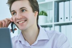 Young white collar talking to customer on mobile phone in office at workplace by laptop. Stock Photography