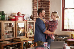 Young white couple embracing in their kitchen Stock Image