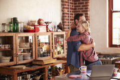 Young white couple hugging in their kitchen Stock Photo