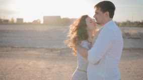 Young white couple in love  on the beach. People look at each other.Man embrace his lady.Woman press to his chest and look at the camera.Slowmotion.Backlight stock footage