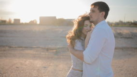 Young white couple in love  on the beach. People look at each other.Man embrace his lady.Woman press to his chest and look at the camera.Slowmotion.Backlight stock video