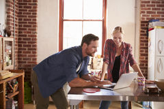 Young white couple using laptop computer in their kitchen Stock Image