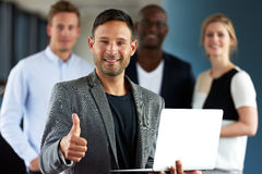 Young white executive making thumbs up sign holding laptop Royalty Free Stock Image