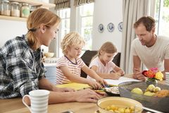 Young white family busy together in their kitchen, close up royalty free stock photo