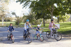 Young white family cycling together through a park Royalty Free Stock Photo