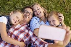 Young white family lying on grass in a park taking a selfie Stock Photo