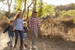 Young white family walking on a path in sunlight, front view Stock Photography