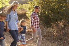 Young white family walking on a path in sunlight, side view Royalty Free Stock Photo