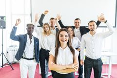 Young white female executive standing with crossed hands in front of colleagues with their arms raised up celebrate win stock image