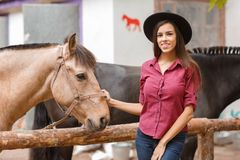 A girl in a hat stands near a horse and smiles. Royalty Free Stock Photography