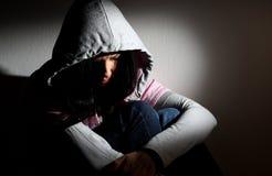 Upset girl in hood. Young white girl sitting looking sad wearing pink sweatshirt with hood royalty free stock photo
