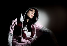 Young girl in hood. Young white girl sitting looking sad wearing pink sweatshirt with hood Royalty Free Stock Images