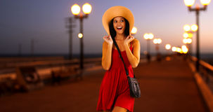 Young white girl standing on the pier in a red sun dress and floppy hat.  Royalty Free Stock Photography