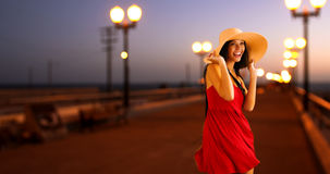 Young white girl standing on the pier in a red sun dress and floppy hat.  Stock Images