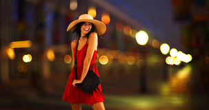 Young white girl standing on the pier in a red sun dress and floppy hat.  Royalty Free Stock Photo