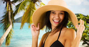 Young white girl in a sun hat poses for a portrait on a Caribbean beach Royalty Free Stock Photo
