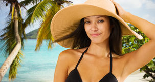 Young white girl in a sun hat poses for a portrait on a Caribbean beach Royalty Free Stock Photography
