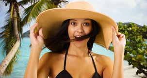 Young white girl in a sun hat poses for a portrait on a Caribbean beach Royalty Free Stock Images