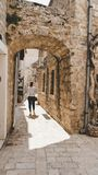 Young white girl taking pictures in the small narrow streets of the old town of Budva, Montenegro. Woman walking between medieval royalty free stock images