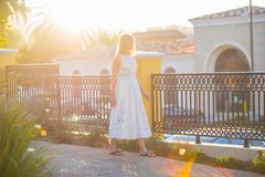Romantic blong girl walking on the street in a beautiful sunset lights. Big copy space for a banner or message. Young white girl walking on the balcony in a stock photos