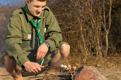 Young White Male Scout Cooking Sausages on Ground Stock Images