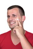 Young white man with moisturizer cream in his face Royalty Free Stock Photo