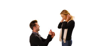Young white man proposes to his girlfriend in front of white background Stock Image