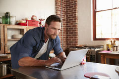 Young white man shopping on-line in kitchen, close up Royalty Free Stock Photography