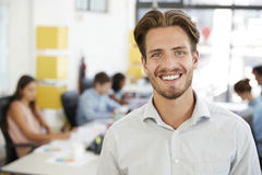 Young white man smiling to camera in an open plan office Royalty Free Stock Photos