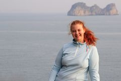Young white red-haired woman in a blue fleece jacket stands against the background of rocks in Halong Bay stock image