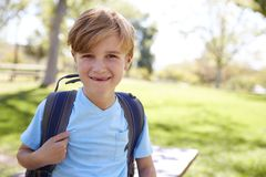Young white schoolboy with backpack smiling to camera royalty free stock image
