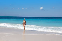 The young in white sexual bikini goes on a peschenny beach against turquoise ocean Stock Photography