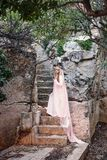 Young white witch queen climbs the stone steps of a fairy-tale staircase in a long dress and a diadem with a veil. A young white witch queen climbs the stone Stock Images