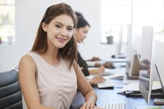 Young white woman with headset smiling to camera in office Stock Images