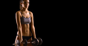 Young white woman lifts weights on a black background with copy space Stock Images