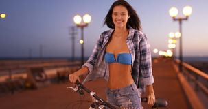 Young white woman poses for a portrait while riding her bicycle on the pier.  stock photos