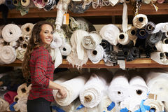 Young white woman selecting fabrics looking to camera Royalty Free Stock Photos