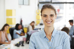 Young white woman smiling to camera in an open plan office Royalty Free Stock Photography