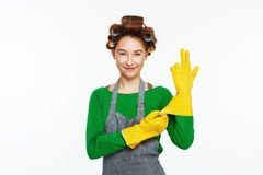 Young white woman wears yeallow rubber gloves and smoles Royalty Free Stock Photos