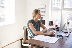 Young white woman working in an office using a computer Stock Image