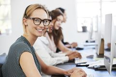 Young white woman with headset smiling to camera in office Royalty Free Stock Photos