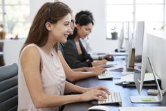 Young white woman working at computer in office with headset. Young white women working at computer in office with headset Stock Photos