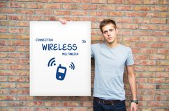 Young with whiteboard multimedia content. Young man holding whiteboard with multimedia content Royalty Free Stock Images