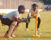 Young cricketers practicing in a field unique photo. A young wicketkeeper is practicing around a cricket ground in the afternoon unique editorial photo stock images