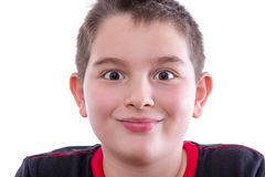 Young Wide Eyed Boy in Studio Smiling at Camera. Head and Shoulders Close Up Portrait of Young Boy Wearing Black and Red Shirt Looking at Camera with Wide Eyes Royalty Free Stock Photo