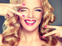 Young wide smiling blonde model. Young wide smiling blonde haired girl-model. Loose, dense, blond hair, red make up and healthy teeth Royalty Free Stock Photography