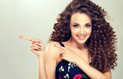 Young, wide smiling brown haired woman is pointing aside. Gesture for advertisement. stock image